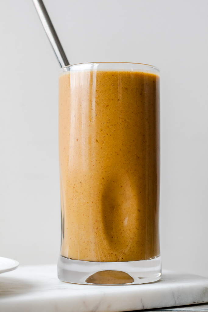 straight on shot of the smoothie in a drinking glass with a steel straw