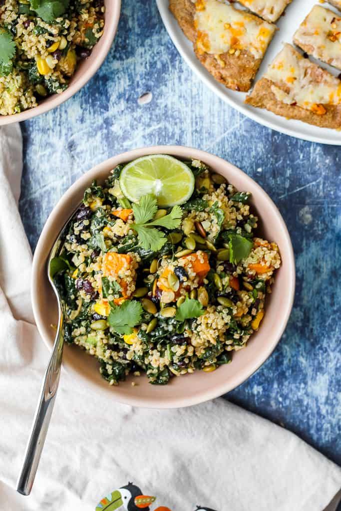 overhead shot of a bowl of quinoa black bean sweet potato salad against a blue backdrop