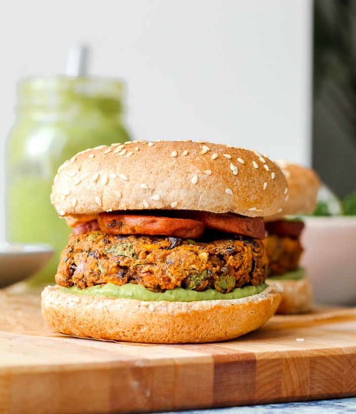 straight on shot of a veggie burger on a bun on a wooden board