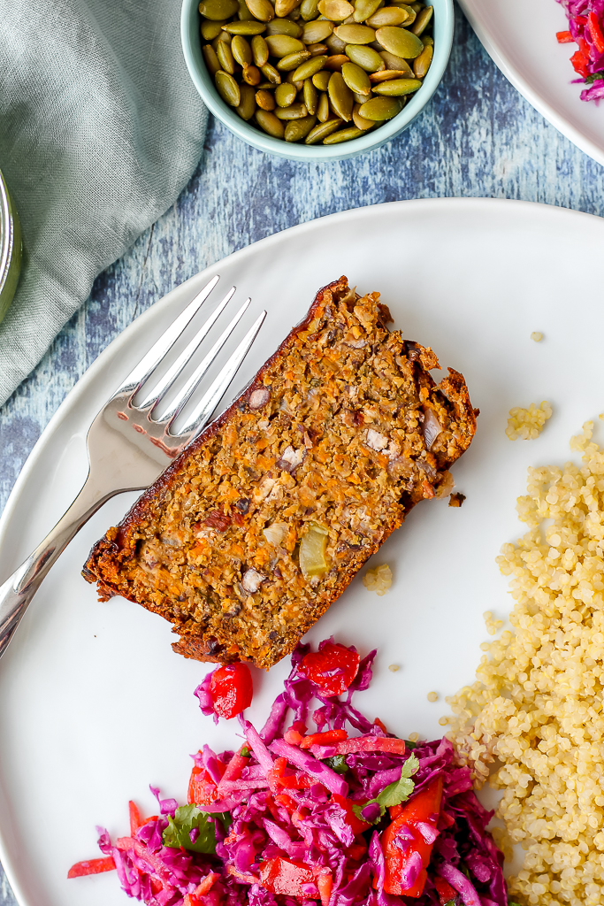 an overhead shot of a slice of the meatloaf on a white plate with quinoa and cabbage slaw on the plate with it