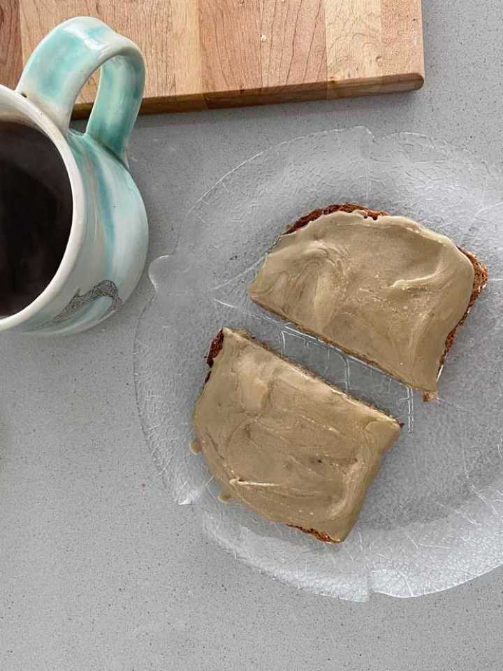 overhead shot of a slice of toast with sunflower seed butter and honey on it with a cup of coffee