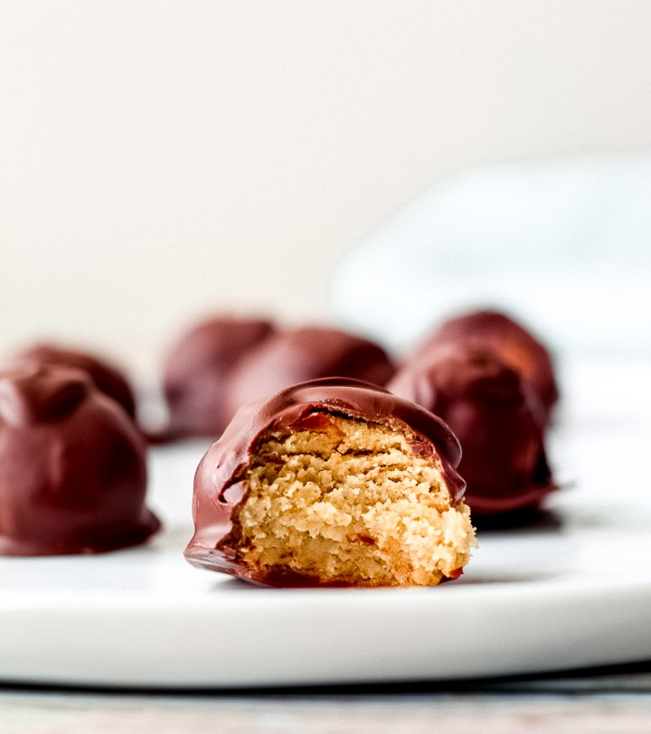 a straight on shot of one of the chocolate tahini maple balls with a bite taken out of it