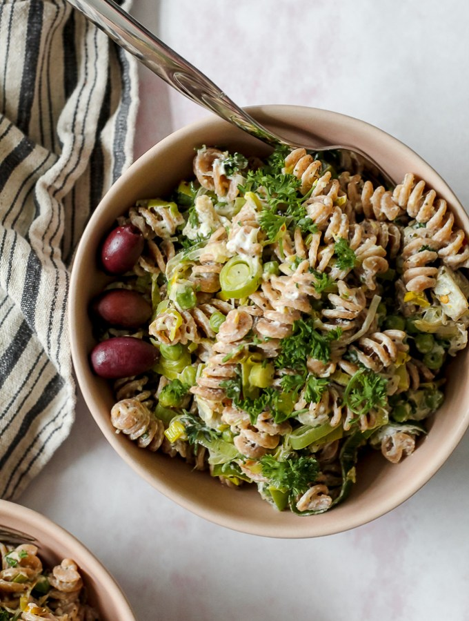 overhead shot of a bowl of creamy goat cheese, leek, and artichoke pasta topped with olives and herbs on a light pink backdrop