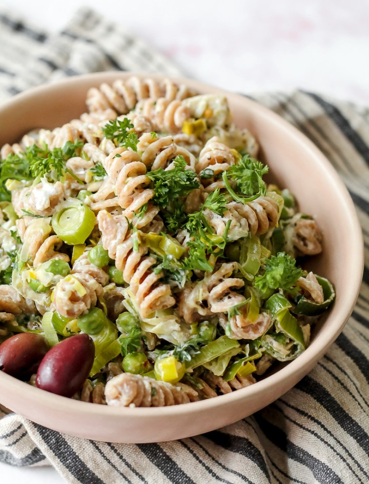 horizontal shot of a bowl of creamy goat cheese pasta with olives and fresh herbs on top
