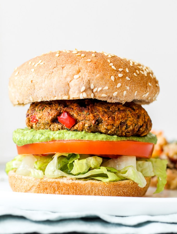 straight on shot of a mediterranean lentil burger with pesto, tomato, and lettuce on a bun