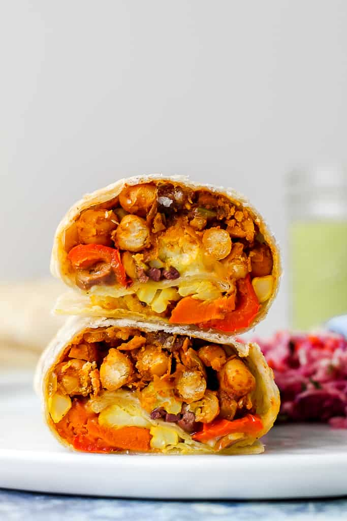 a straight on shot of two halves of Moroccan chickpea burrito stacked on a white plate