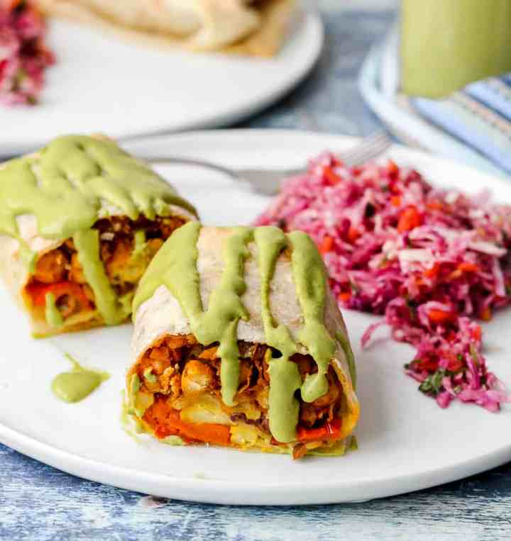 straight on shot of two halves of moroccan chickpea burrito on a white plate with a side of cabbage slaw