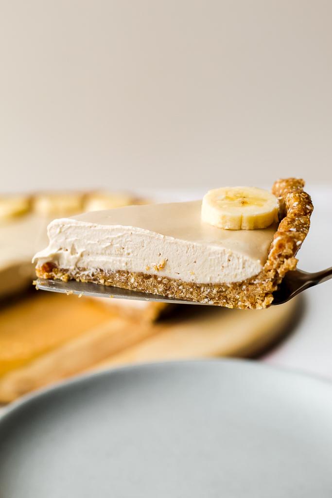 straight on shot of a slice of raw vegan banana cream pie on a server