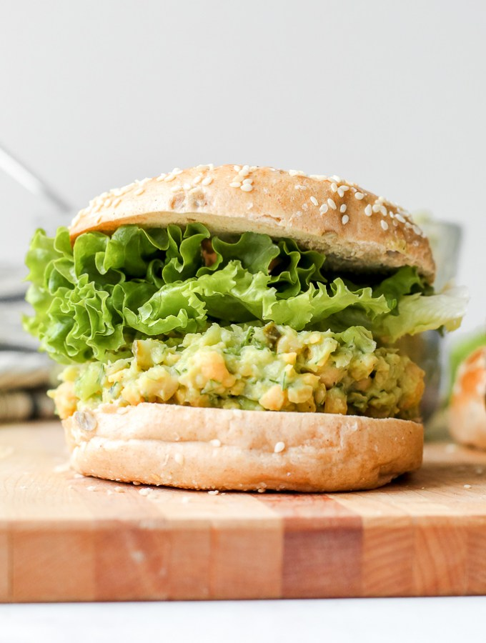 a straight on shot of the smashed chickpea avocado sandwich on a bagel on a wooden board