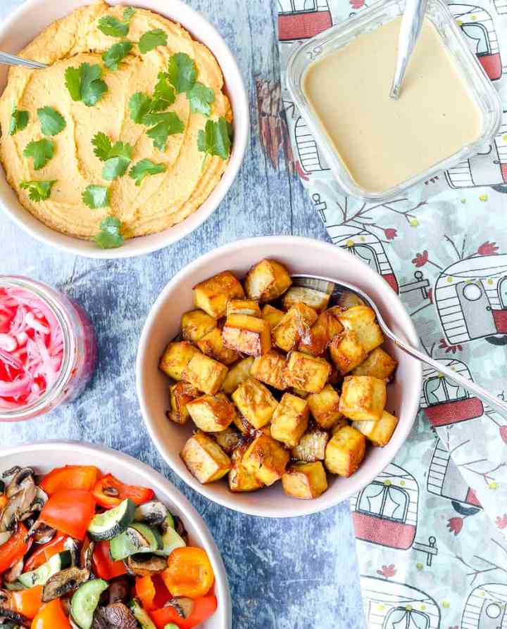 an overhead shot of bowls of red curry peanut hummus, tofu, roasted veggies, pickled onions, and pita sauce on a blue backdrop