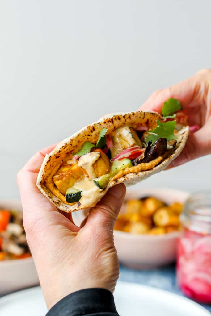 straight on shot of someone holding a Thai tofu red curry hummus pita in someone's hands