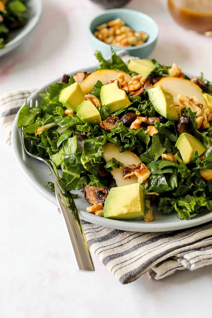 a straight on shot of a serving of the spinach, roasted mushroom and walnut salad with avocado and pear slices on a blue plate