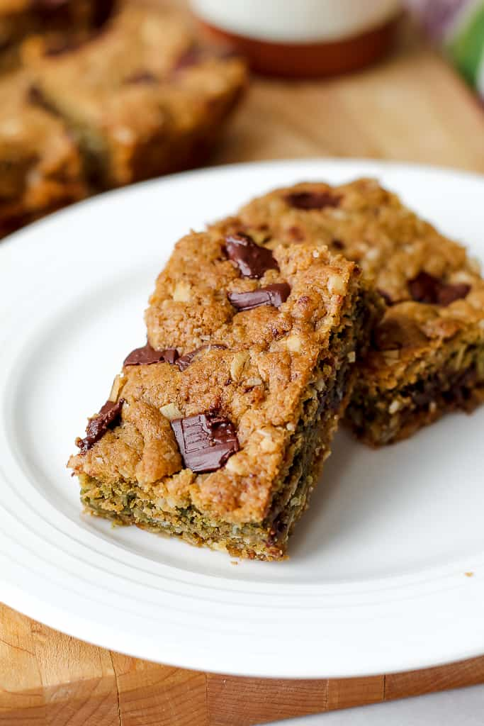straight on shot of a couple of chocolate chunk oatmeal cookie bars on a white plate