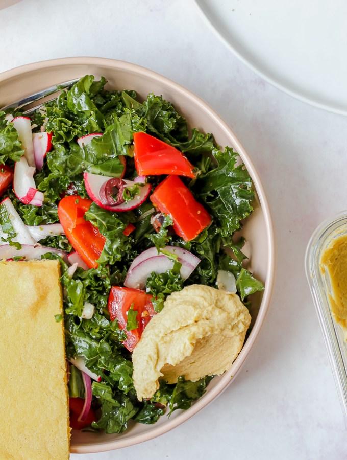 close up overhead shot of Greek kale salad in a bowl on a light pink backdrop