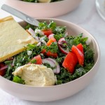 straight on shot of a bowl of the Greek kale salad with a dollop of hummus and a big wedge of socca