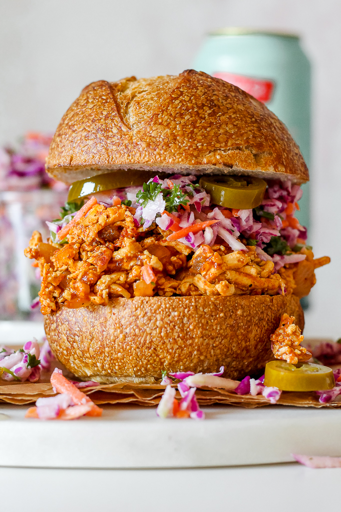 straight on close up of a bbq pulled tofu sandwich on a white bun with kohlrabi slaw on top