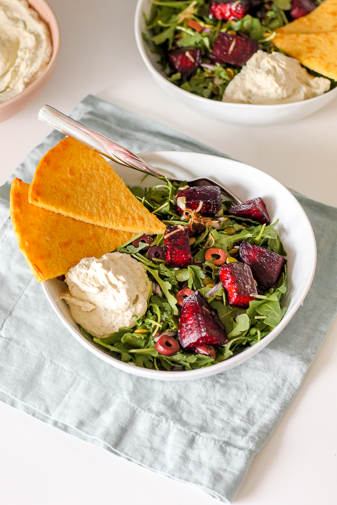 straight on shot of two bowls with arugula salad, roasted beets and whipped tofu