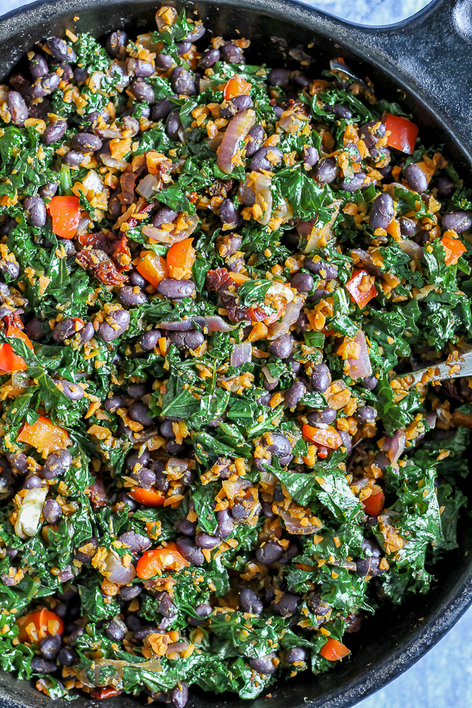 overhead photo of skillet of beans, carrot rice, and kale