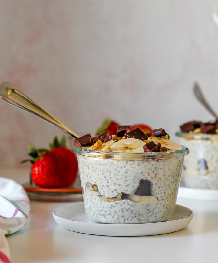 straight on shot of two bowls of the chunky monkey overnight oats, one in the foreground and one in the background, with strawberries in behind