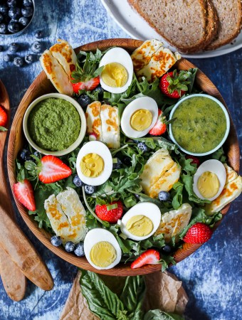 overhead photo of a big salad bowl full of the egg, halloumi and berry baby kale salad on a dark blue backdrop