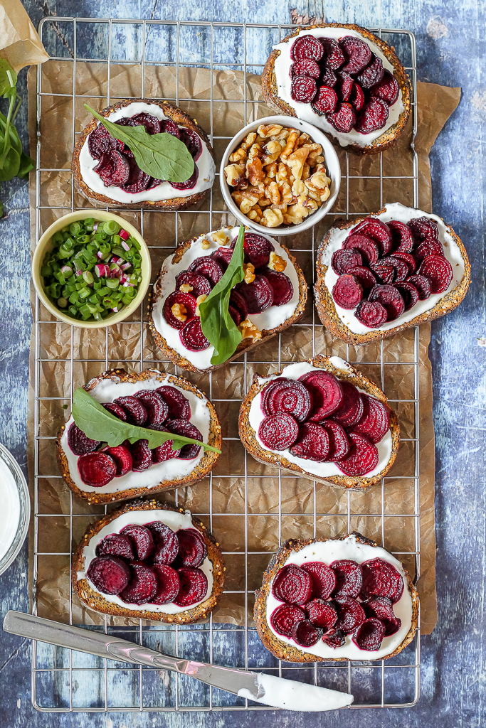 an overhead shot of the beet goat cheese crostini on a wire rack set against a blue background