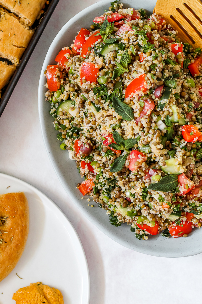 overhead shot of a platter of lentil quinoa tabbouleh and a plate of focaccia