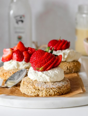 straight on shot of oat flour biscuits topped with honey whipped cream and strawberries on a white marble