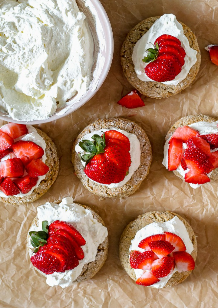 an overhead shot of the biscuit strawberry shortcakes on a piece of parchment paper with a big bowl of whipped cream
