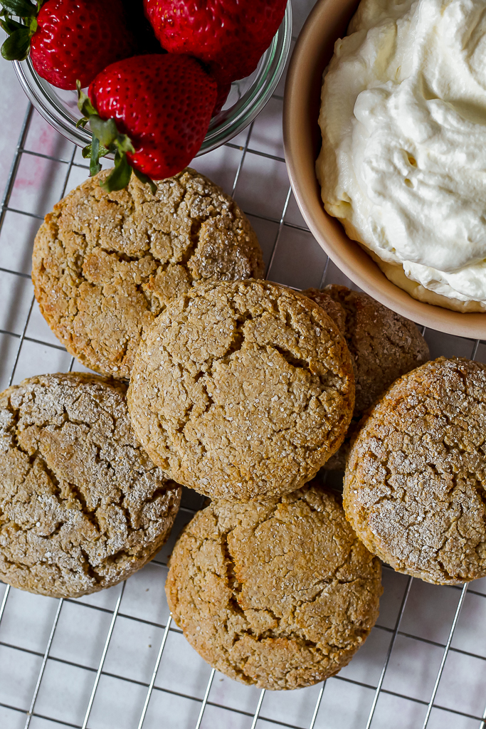 an overhead shot of the oat flour biscuits on a wire rack with a bowl of whipped cream and strawberries