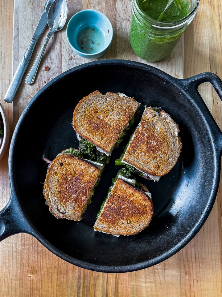 overhead shot of the cooked broccoli, brie and pesto grilled cheese in a cast iron skillet
