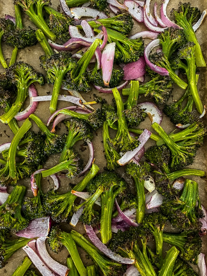 overhead shot of the roasted broccoli and onion on a baking sheet