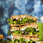 straight on shot of the pesto, brie, and roasted broccoli grilled cheese sandwiches stacked on top of each other on a wooden board