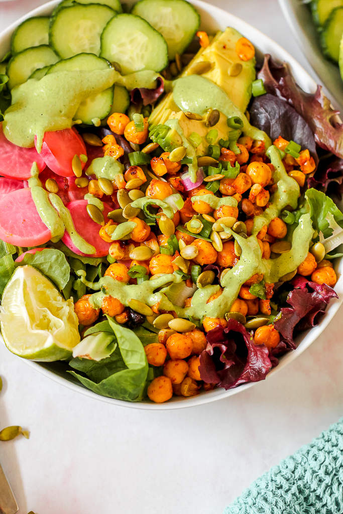 close up of a bowl of the salad showing detail of the roasted chickpeas and corn as well as the green dressing