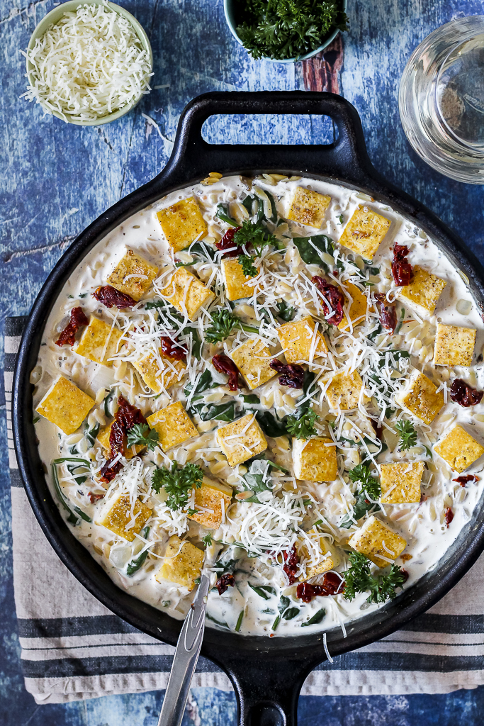 overhead photo of the creamy one skillet orzo and tofu surrounded by a glass of wine and a small dish of cheese