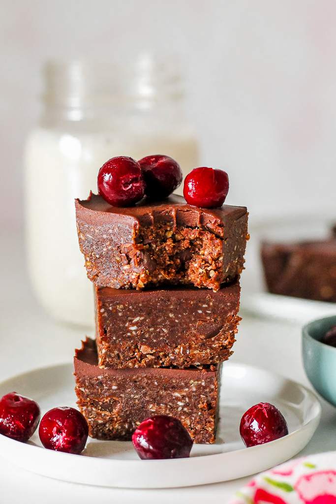 straight on shot of a stack of three brownies on a small white plate