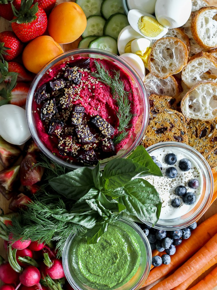 overhead photo of a close up of the three dips on a wooden board surrounded by veggies, baguette, and crackers.