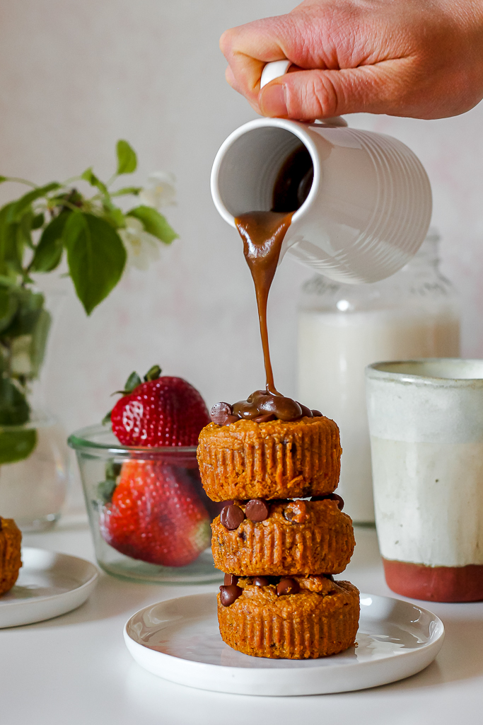 a photo of vegan caramel sauce poured over top of a stack of three vegan sweet potato oat flour blondies on a white plate