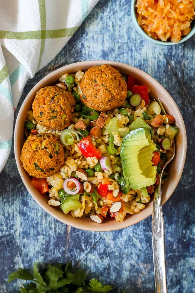 overhead shot of an individual serving of the kimchi brown rice salad in a bowl topped with salmon balls