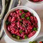 overhead photo of the creamy beet lentil pasta with feta sauce in a white bowl on a pink backdrop