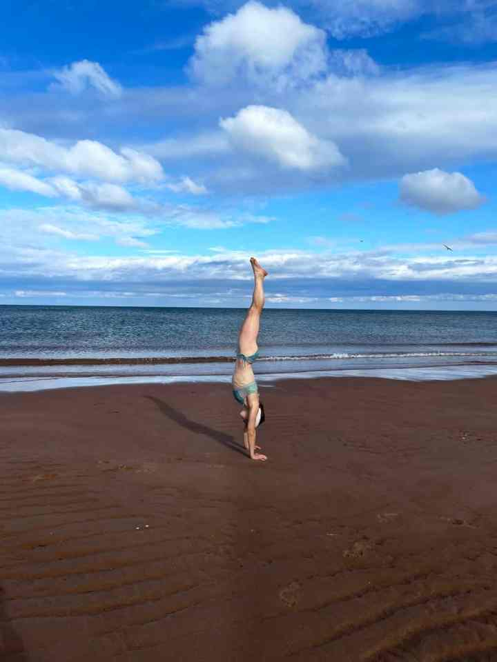 Allison doing a handstand on a beach in PEI