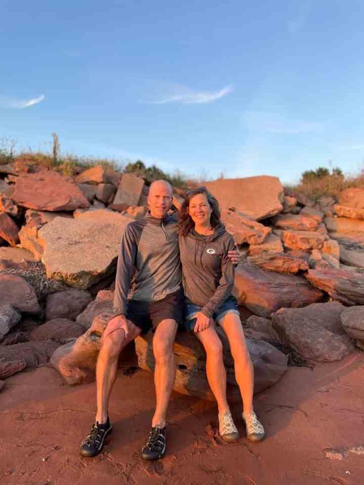 a couple sitting on a rock on a beach in Prince Edward Island