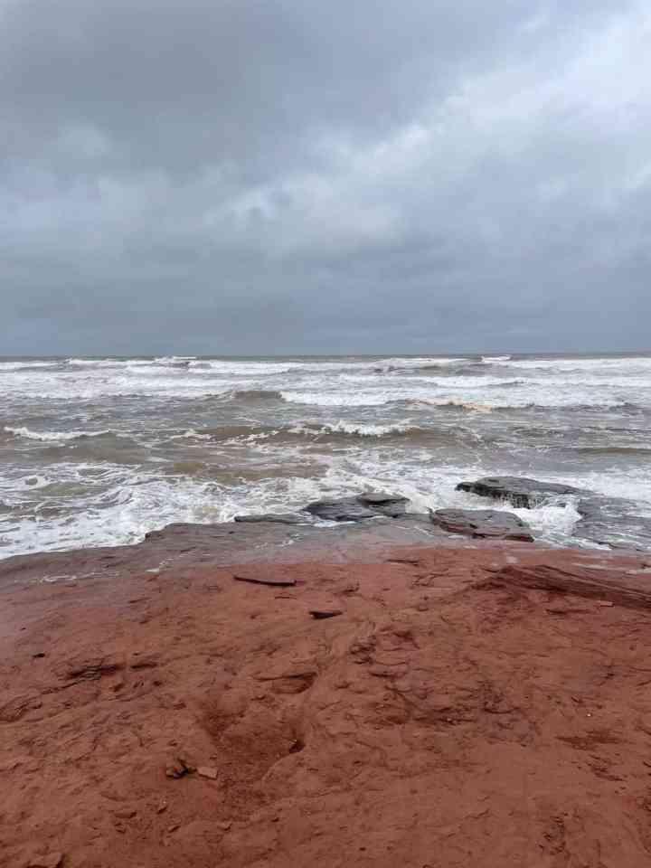 a stormy PEI sea crashing onto red rocks