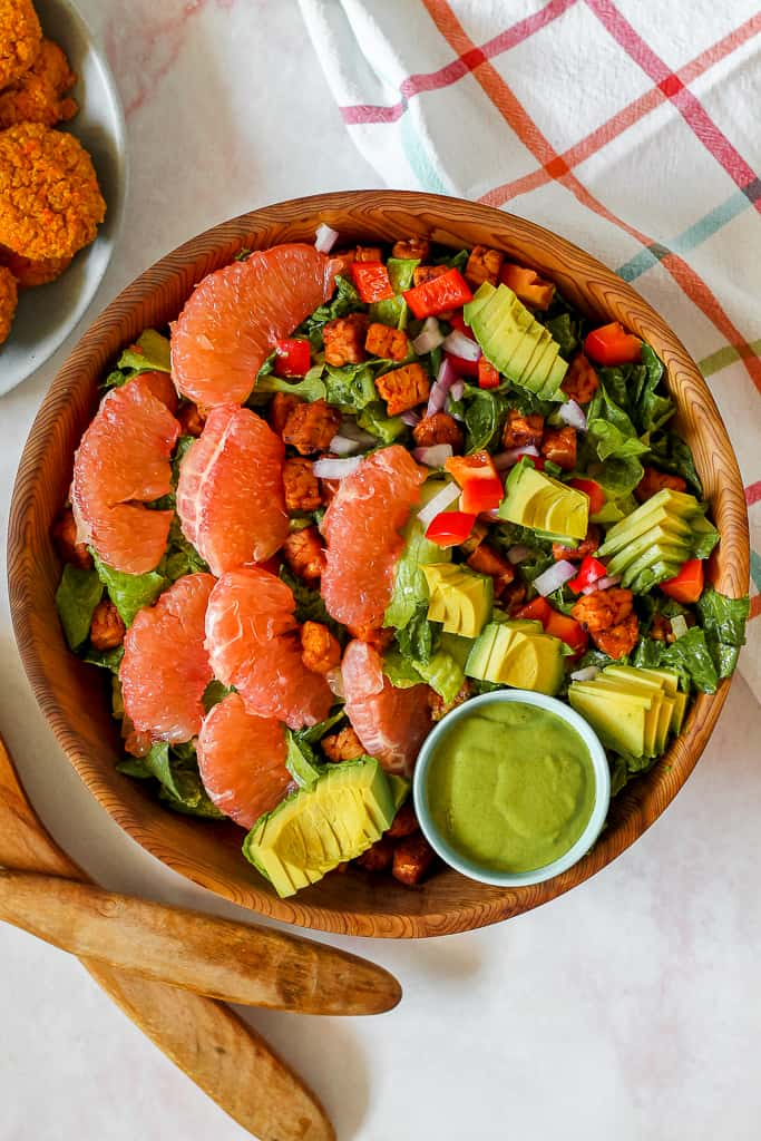 overhead shot of the salad with tempeh, grapefruit, avocado, and lettuce in a big cedar wood bowl on a pink backdrop