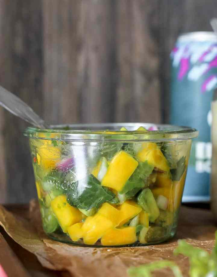 straight on shot of a container of mango avocado salsa