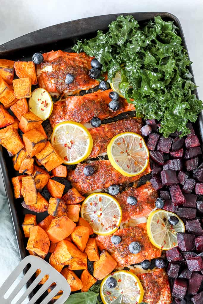 overhead shot of the sheet pan salmon on a baking sheet surrounded by the roasted root veggies and kale