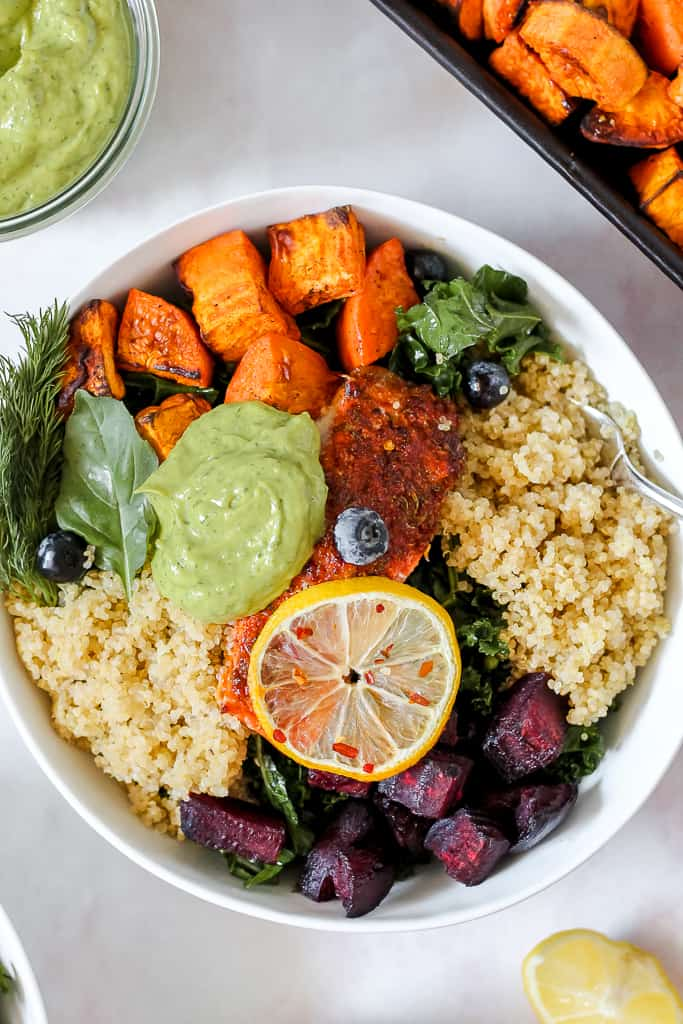 close-up overhead photo of the salmon in a bowl topped with avocado sauce and served with quinoa, root veggies, and kale