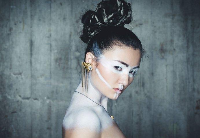 Modefoto asiatisches Model trägt goldenen Ohrring