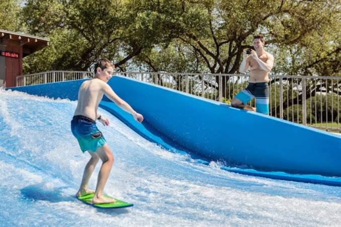 Boy rides a waterboard in FlowRider fun at the Hyatt Regency Hill Country Resort & Spa.