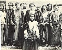 السلطان تيمور بن فيصل و خلفه بعض شيوخ عمان.jpg
