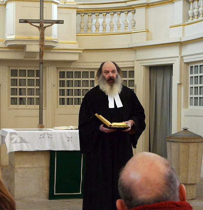 German city of Jena, Thuringia's Local Luthran youth Pastor Lothar König in clerical robe on the altar